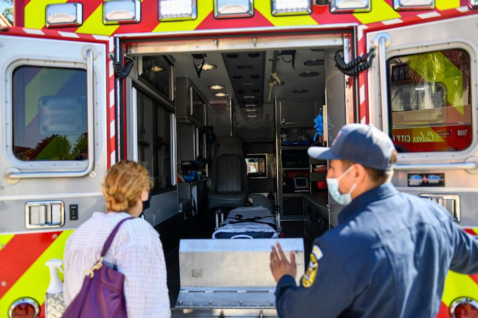 A person receives a tour of the station's rescue ambulance from a paramedic after they received a dose of the Johnson and Johnson Janssen Covid-19 vaccine at a Culver City Fire Department vaccination clinic on August 5, 2021, in California. (Photo by Patrick T. FALLON / AFP) (Photo by PATRICK T. FALLON/AFP via Getty Images)