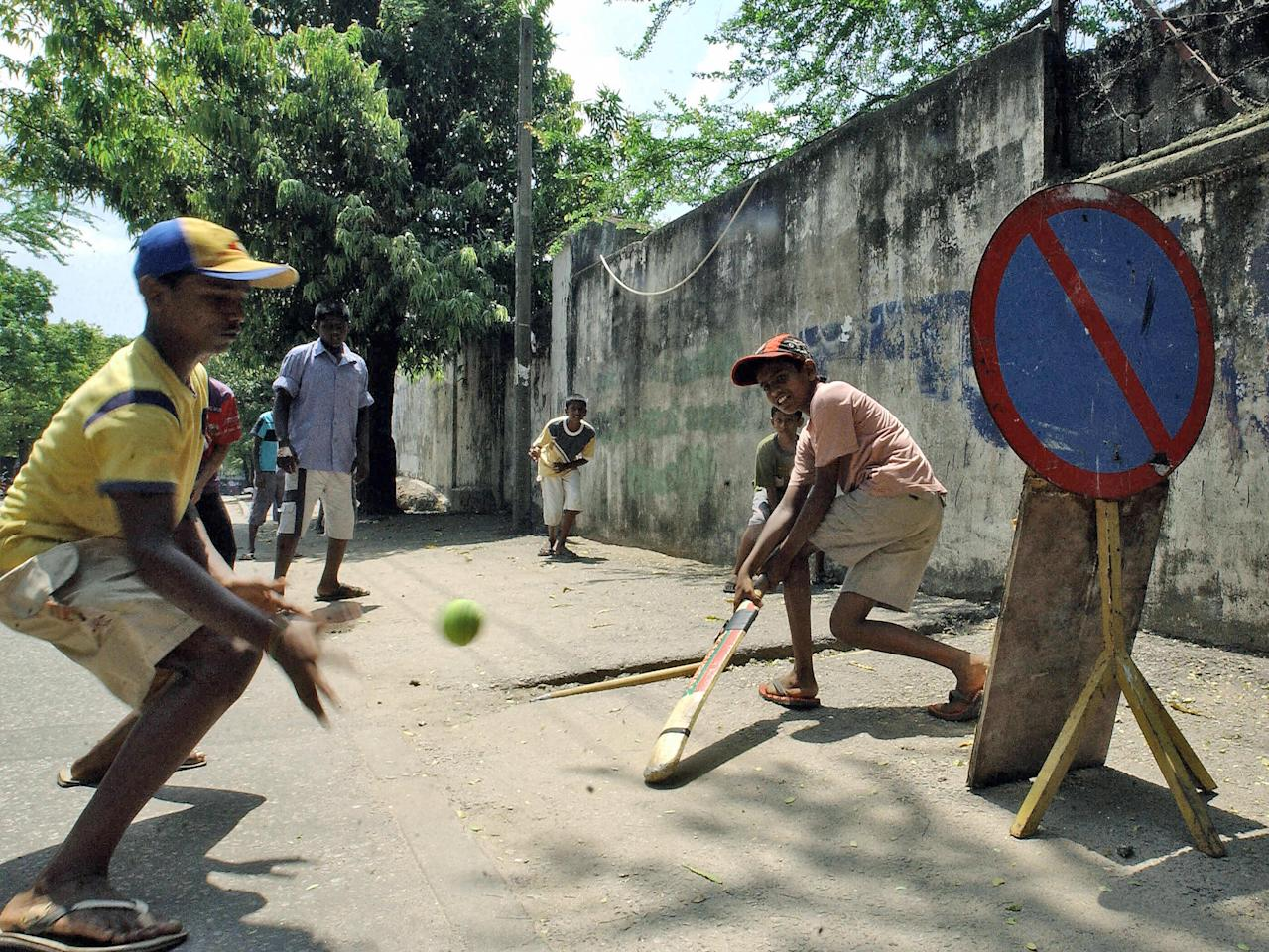 Colombo, SRI LANKA: TO GO WITH CRICKET-WC2007-SRI-UNREST-FEATURE  Sri Lankan children play a cricket match on the streets of Colombo, 20 April 2007.  Sri Lankans treat cricket as a religion, but the sport has failed to heal wounds of this deeply divided nation despite its ethnically-mixed World Cup squad displaying strong unity.The success of Sri Lanka's multi-ethnic team at the ongoing tournament is seen as an example of shedding communal differences, but not many are optimistic that it will stop the bloodshed.   AFP PHOTO/Sanka VIDANAGAMA (Photo credit should read SANKA VIDANAGAMA/AFP/Getty Images)