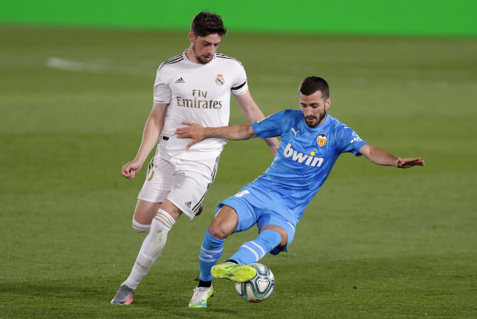 Real Madrid's Federico Valverde, left, challenges for the ball with Valencia's Jose Luis Gaya during the Spanish La Liga soccer match between Real Madrid and Valencia at Alfredo di Stefano stadium in Madrid, Spain, Thursday, June 18, 2020. (AP Photo/Manu Fernandez)