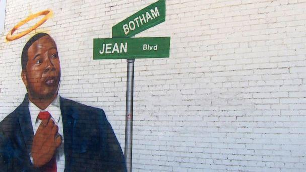 PHOTO: A mural depicts the late Botham Jean and a street sign with his name on it, March 26, 2021, in Dallas. (WFAA)