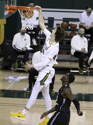 Baylor guard Matthew Mayer (24) scores past Central Arkansas forward Samson George (23) in the second half of an NCAA college basketball game, Tuesday, Dec. 29, 2020, in Waco, Texas. (AP Photo/ Jerry Larson)