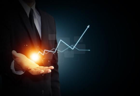 A spark and two digital graph arrows rising from a businessman's hand.