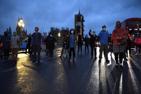 People wearing face masks and holding lanterns attend a vigil for the victims of the coronavirus on Westminster Bridge on 3 July 2020 in London, England (Photo by Chris J Ratcliffe/Getty Images)