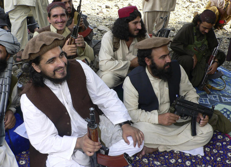 FILE - In this file photo taken Sunday, Oct. 4, 2009, new Pakistani Taliban chief Hakimullah Mehsud, left, is seen with his comrade Waliur Rehman, front center, during his meeting with media in Sararogha of Pakistani tribal area of South Waziristan along the Afghanistan border. Intelligence officials said Friday, Nov. 1, 2013 that the leader of the Pakistani Taliban Hakimullah Mehsud was one of three people killed in a U.S. drone strike. (AP Photo/Ishtiaq Mehsud, File)