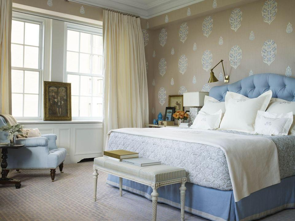 """<p>In this New York master bedroom, designer and architect Daniel Romualdez creates a soothing sleep space by using a neutral palette of blue, cream, and taupe. The patterned walls bring out the sky blue <a href=""""https://fave.co/2PvBxC0"""" rel=""""nofollow noopener"""" target=""""_blank"""" data-ylk=""""slk:Rogers & Goffigon"""" class=""""link rapid-noclick-resp"""">Rogers & Goffigon </a>fabric on the custom headboard and chair. The Louis XVI bench features a <a href=""""https://fave.co/2Dz3hRm"""" rel=""""nofollow noopener"""" target=""""_blank"""" data-ylk=""""slk:Le Crin"""" class=""""link rapid-noclick-resp"""">Le Crin</a> stripe. The curtains are in a <a href=""""https://fave.co/2vkXzNq"""" rel=""""nofollow noopener"""" target=""""_blank"""" data-ylk=""""slk:Manuel Canovas"""" class=""""link rapid-noclick-resp"""">Manuel Canovas</a> fabric.</p>"""