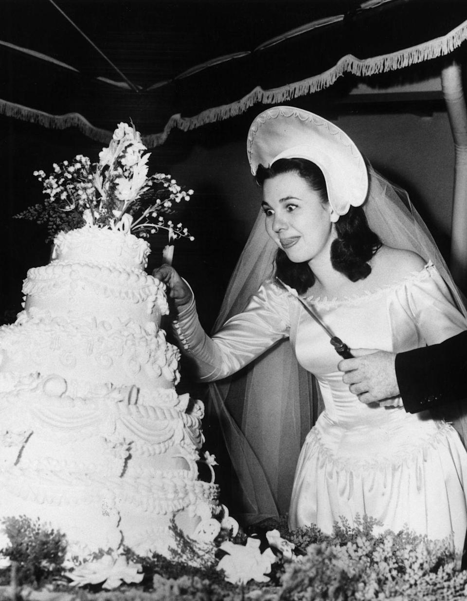 <p>This 1947 bride can't quite believe her eyes at the tiered cake in front of her. It was designed to feed 600 of her guests! (Our attention shifts to her very unusual hat, though.)</p>