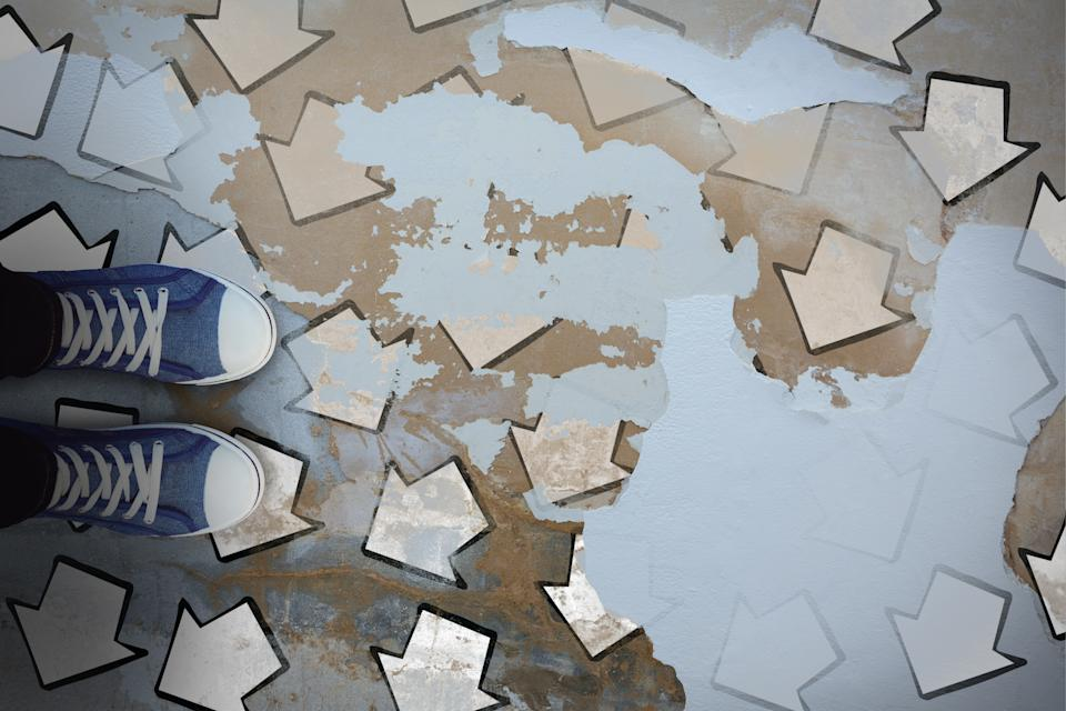 High angle view of person wearing canvas shoes against rusty weathered street. (Photo: Getty Images)