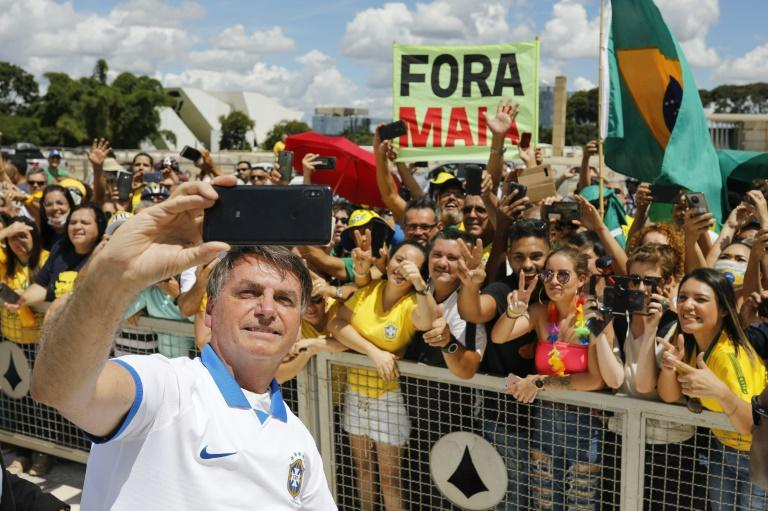 Brazilian President Jair Bolsonaro has come under fire for taking selfies with supporters at a rally, even after his own aides recommended he remain in isolation