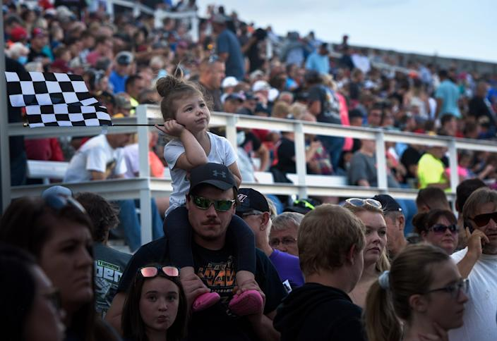 Deyvani Haeffner waits in line atop father Steven's shoulders at Huset's Speedway during its opening night Sunday in Brandon, S.D. The track had been closed since 2017.