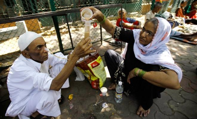 A 68-year-old man suffering from throat cancer gets help outside a cancer hospital in Mumbai on April 1.