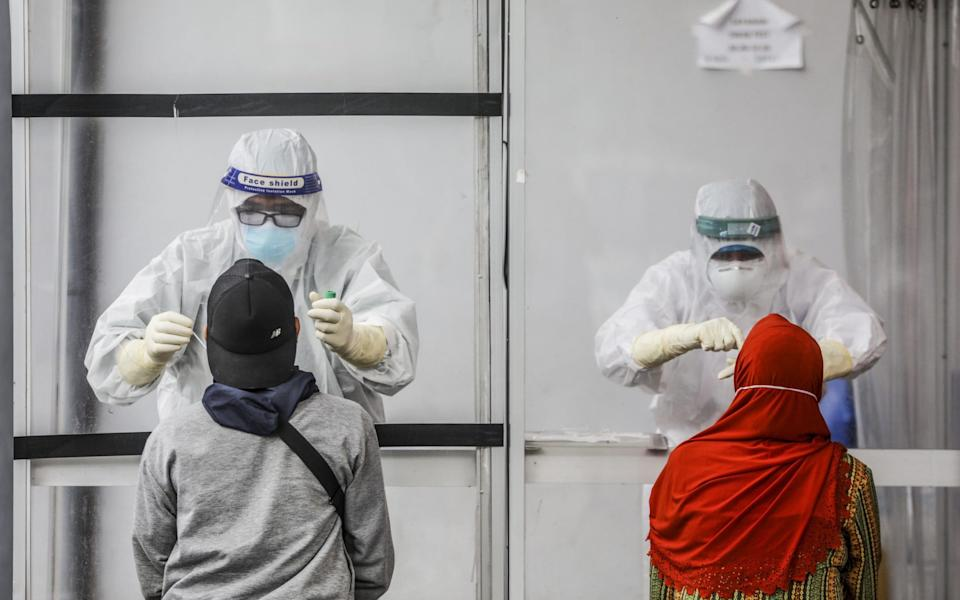 Healthcare workers in hazmat suits collect specimen samples through a plexiglass wall during a Covid-19 swab test in Medan, North Sumatra, Indonesia - Dedi Sinuhaji/EPA-EFE/Shutterstock