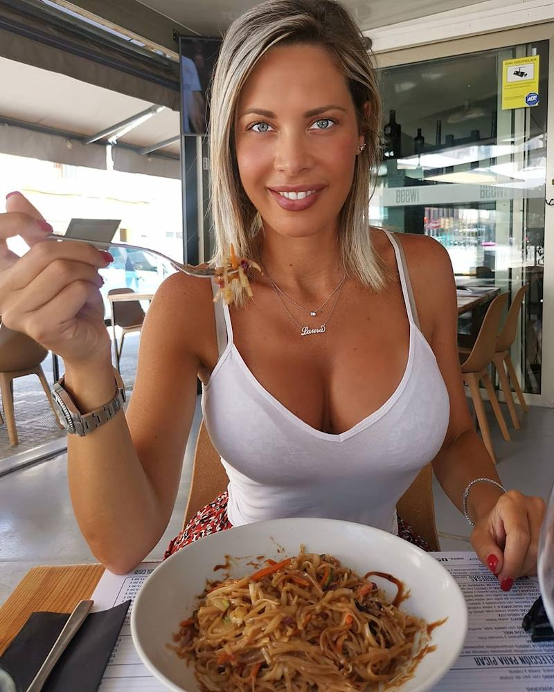 Woman in a white string top eating pasta