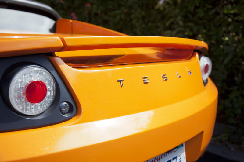 Palo Alto, California, USA - July 19, 2011: An exterior look at the rear end of an orange convertible Tesla Roadster electric sports car. The Roadster was designed in partnership with Lotus and debuted in 2008 and had a sticker price of around $100,000 dollars. Tesla plans to continue to sell the cars through 2012.