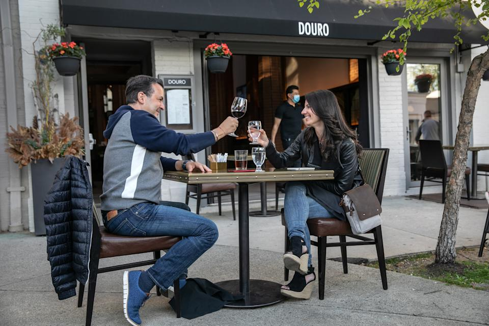 GREENWICH, CONNECTICUT - MAY 20: A couple toasts at an outdoor table at Douro restaurant on May 20, 2020 in Greenwich, Connecticut. After two months of lockdown due to the coronavirus pandemic, Connecticut partially reopened some businesses today, one of the last states to begin to do so. Restaurants can now serve patrons at outdoor seating at socially-distanced tables. Employees must wear masks.  (Photo by John Moore/Getty Images)