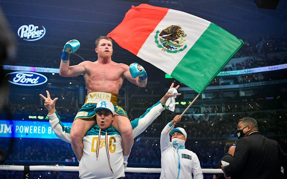 Canelo is held aloft after the fight - USA TODAY Sports