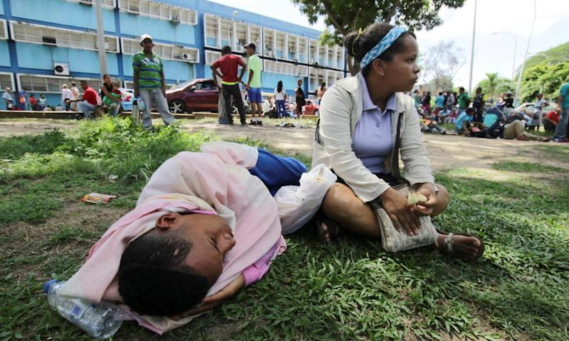 People lie on the grass outside a San Felix health centre, waiting for malaria treatment