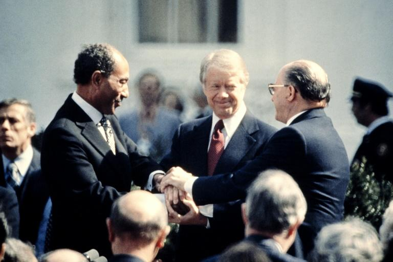 US President Jimmy Carter is between Egypt's President Anwar Sadat (L) and Israeli Prime Minister Menachem Begin (R) at the signature of the Egypt-Israel Peace Treaty on March 26, 1979