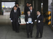 Relatives and friends of the late mountain climber Kim Chang-ho carry his portrait and the casket containing his body from a cargo terminal at Incheon International Airport in Incheon, South Korea, Wednesday, Oct. 17, 2018. Relatives dressed in black funeral suits wept in grief on Wednesday as the bodies of five South Korean mountain climbers arrived home from Nepal where they had died in a storm last week. (Lee Ji-eun/Yonhap via AP)