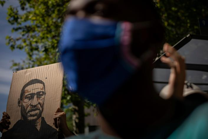 A demonstrator holds a George Floyd placard in front of the American embassy in Madrid on June 7, 2020, during a demonstration over the death of George Floyd and victims of racial injustice.