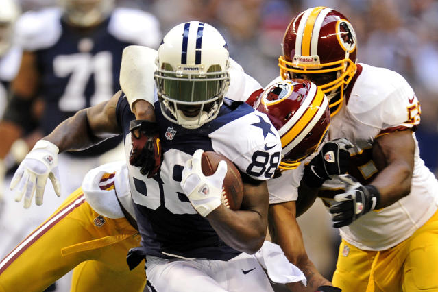 Dallas Cowboys wide receiver Dez Bryant (88) tries to break a tackle by Washington Redskins' Cedric Griffin, rear, and London Fletcher, right, after a reception in the first half of an NFL football game, Thursday, Nov. 22, 2012, in Arlington, Texas. (AP Photo/Matt Strasen)