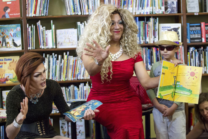 Blazen Haven, left, and Vanessa Carr read to children, including Ryan Banks, 7, right, during Drag Queen Story Time at the Alvar Library in New Orleans on Saturday, Aug. 25, 2018. Children and parents and caregivers packed into the library to hear stories and sing songs during the event. (Scott Threlkeld/The Advocate via AP)