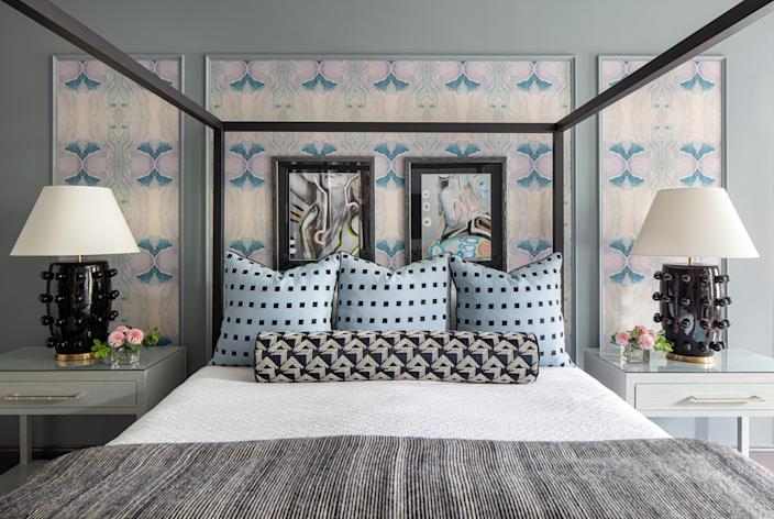 """Walls coated in a soothing Benjamin Moore Gibraltar Cliffs pair well with Lindsay's blue and purple Caribbean Grasscloth wall covering. """"The wallpaper over the bed is the same color as the walls, but just a little touch of pattern,"""" Jill says. The painted photographs are by artist Allison Hobbs. The Room & Board Architecture Bed is topped with Kelly Wearstler blue pillows, a black-and-white Schumacher bolster, and a Rebecca Atwood blanket. Custom nightstands are topped with Kelly Wearstler lamps."""