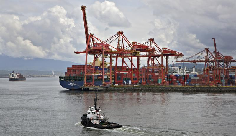 A tugboat heads out into the harbour beside the container port in Vancouver