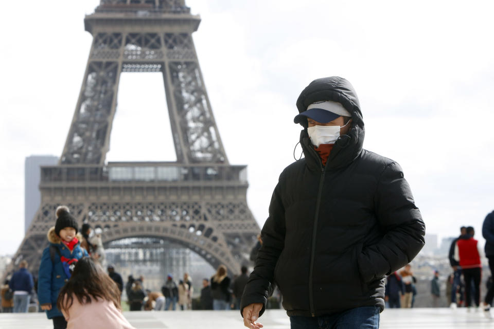 People wear a face mask on the Trocadero esplanade in front of the Eiffel Tower in Paris, France, March 3, 2020, as France confirmed a more than 200 persons infected with coronavirus, on February 29 in France. (Photo by Mehdi Taamallah/NurPhoto via Getty Images)