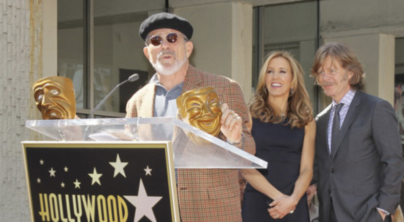 David Mamet spoke in 2012 when Felicity Huffman and husband William H. Macy (in the background) received their stars on the Hollywood Walk of Fame. (Michael Tran via Getty Images)