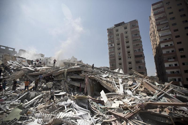 Palestinians look through the rubble of a 12-storey apartment building in Gaza City on August 24, 2014 that collapsed after it was hit by an Israeli air strike the day before