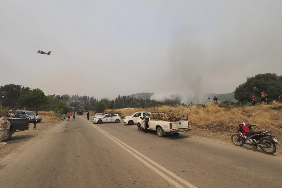 An aircraft operates as police blocks a road during a wildfire in Kourkouloi village on the island of Evia, about 150 kilometers (93 miles) north of Athens, Greece, Thursday, Aug. 5, 2021. Forest fires fueled by a protracted heat wave raged overnight and into Thursday in Greece, threatening the archaeological site at the birthplace of the modern Olympics and forcing the evacuation of dozens of villages. (AP Photo/Thodoris Nikolaou)