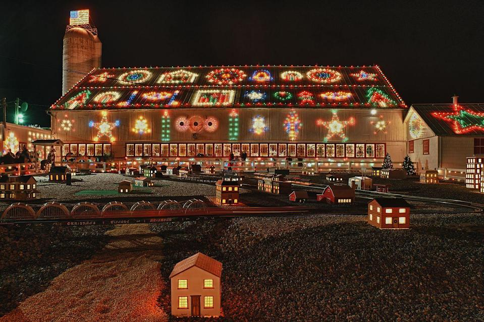 """<p>Driving on the dark unlit country road, you may think you're in the wrong place, but just over the last hill, you'll find yourself transported to the Christmas house of your dreams. William Koziar began creating <a href=""""https://koziarschristmasvillage.com/history/"""" rel=""""nofollow noopener"""" target=""""_blank"""" data-ylk=""""slk:Koziar's Christmas Village"""" class=""""link rapid-noclick-resp"""">Koziar's Christmas Village</a> in 1948, which has since become a Christmas spectacular. Every inch of the Koziar property is lit up — from the barn to lakes, walkways, trees, fences, and buildings. Sip on a cup of hot cocoa, check out the stunning lights, and enjoy Christmas music from around the world as you marvel at the Koziar family's creation. <br></p>"""