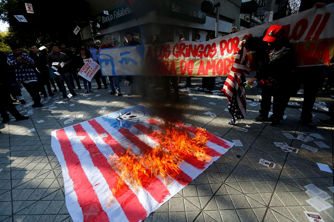 Demonstrators set a U.S. flag on fire during a protest against the visit of U.S. Vice President Mike Pence in Santiago, Chile August 16, 2017. REUTERS/Carlos Vera