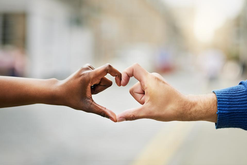 Closeup shot of an unrecognizable couple making a heart shape with their hands outside
