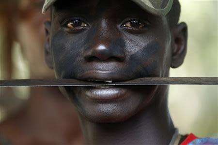 "A fighter from the Christian ""anti-balaka"" militia holds a machete in his mouth at the headquarters in the northern Bangui suburb of Boeing, an area near the Mpoko International Airport of Bangui February 22, 2014. REUTERS/Luc Gnago"