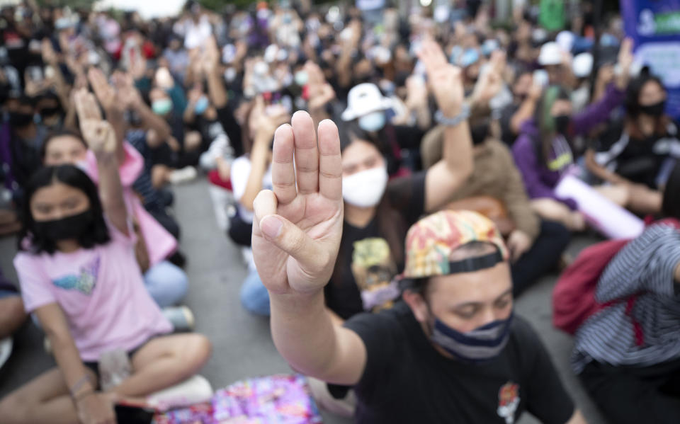 Pro-democracy activists flash three-fingered salutes outside remand prison, in which some of the activists are kept, in Bangkok, Thailand, Friday, Oct. 23, 2020. Thailand's government on Thursday canceled a state of emergency it had declared last week for Bangkok in a gesture offered by the embattled prime minister to cool student-led protests seeking democracy reforms. (AP Photo/Sakchai Lalit)