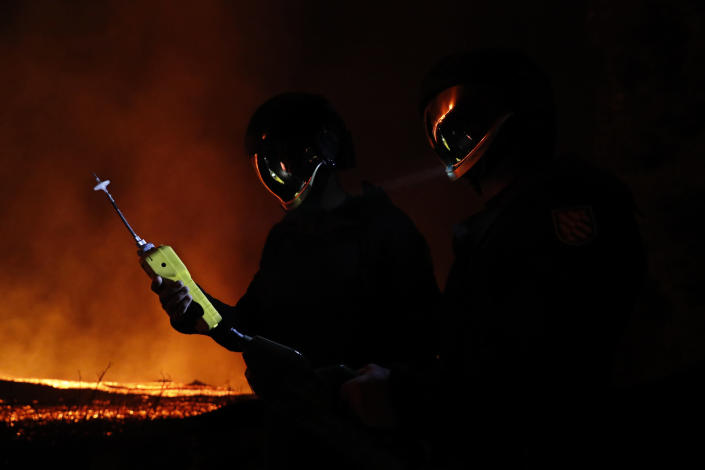 In this photo made available by Ume (Unidad Militar de Emergencias), Military Emergency Unit personal take gas reading measurements near a volcano on the Canary island of La Palma, Spain, in the early hours of Tuesday Sept. 28, 2021. Lava flowing from an erupting volcano on the Spanish island of La Palma has picked up pace on its way to the sea. Officials say it is now within about 800 meters (875 yards) of the shoreline. When the molten rock eventually meets the sea water it could trigger explosions and toxic gas. (Luismi Ortiz/UME via AP)