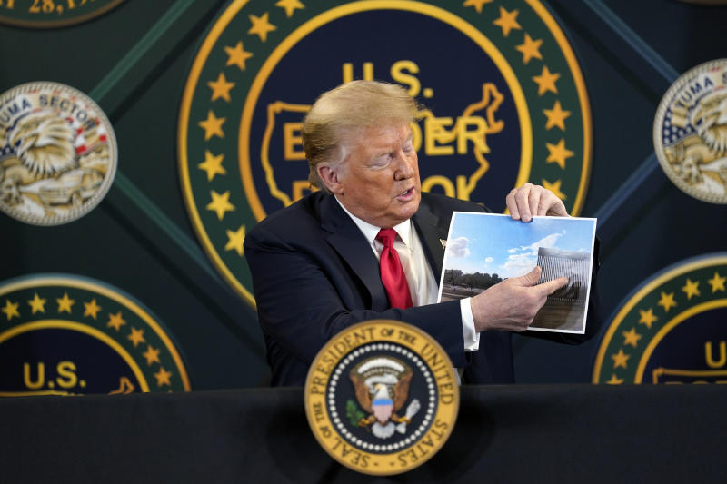 President Donald Trump holds an image of the U.S. border wall being built between the U.S. and Mexico as he participates in a border security briefing at United States Border Patrol Yuma Station, Tuesday, June 23, 2020, in Yuma, Ariz. (AP Photo/Evan Vucci)