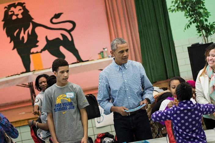 US President Barack Obama helps give out books to children at Leckie Elementary School while celebrating Martin Luther King Day on January 18, 2016 in Washington, DC (AFP Photo/Brendan Smialowski)
