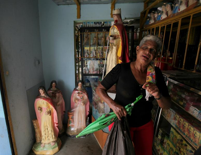 In this April 25, 2013 photo, Zaida Eleonora Mejicano, a shop owner in the coastal town of Moron, complains of shortages of food and medicine in her town, which sits right next to Puerto Cabello, Venezuela. Venezuelans across the country are suffering from a drop in the price of oil, the country's main source of foreign exchange and the resource that has allowed the government to go on a long spending spree that won it widespread support throughout much of the presidency of the late Hugo Chavez. (AP Photo/Fernando Llano)