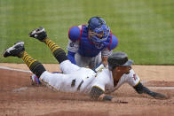 Los Angeles Dodgers catcher Austin Barnes, top, tags out Pittsburgh Pirates' Erik Gonzalez who was attempting to score on a fly out to right field by Ka'ai Tom during the second inning of a baseball game in Pittsburgh, Thursday, June 10, 2021. (AP Photo/Gene J. Puskar)