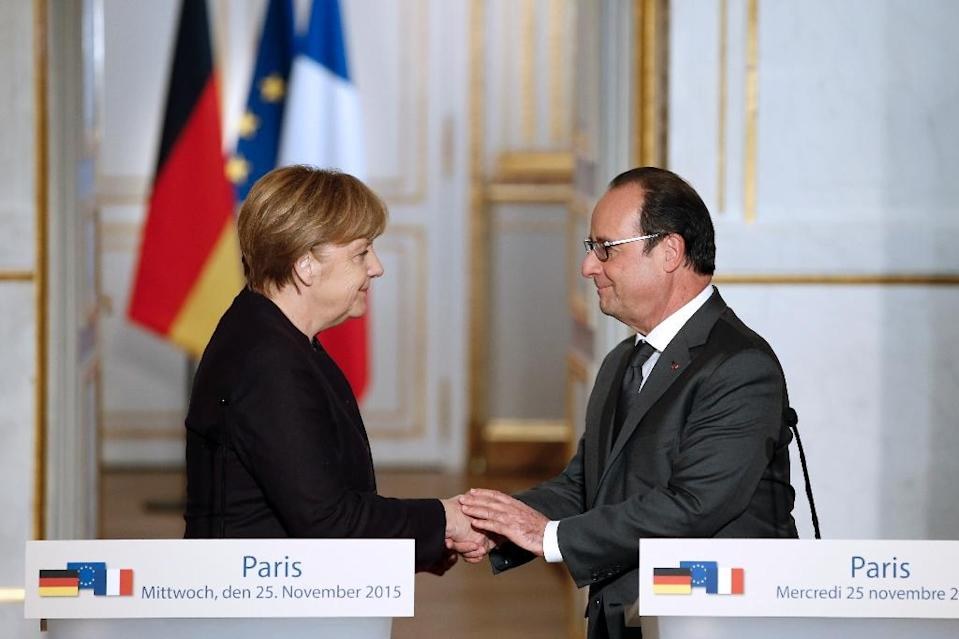 French President Francois Hollande (R) shakes hands with German Chancellor Angela Merkel after a joint press conference at the Elysee presidential palace in Paris, on November 25, 2015 (AFP Photo/Patrick Kovarik)