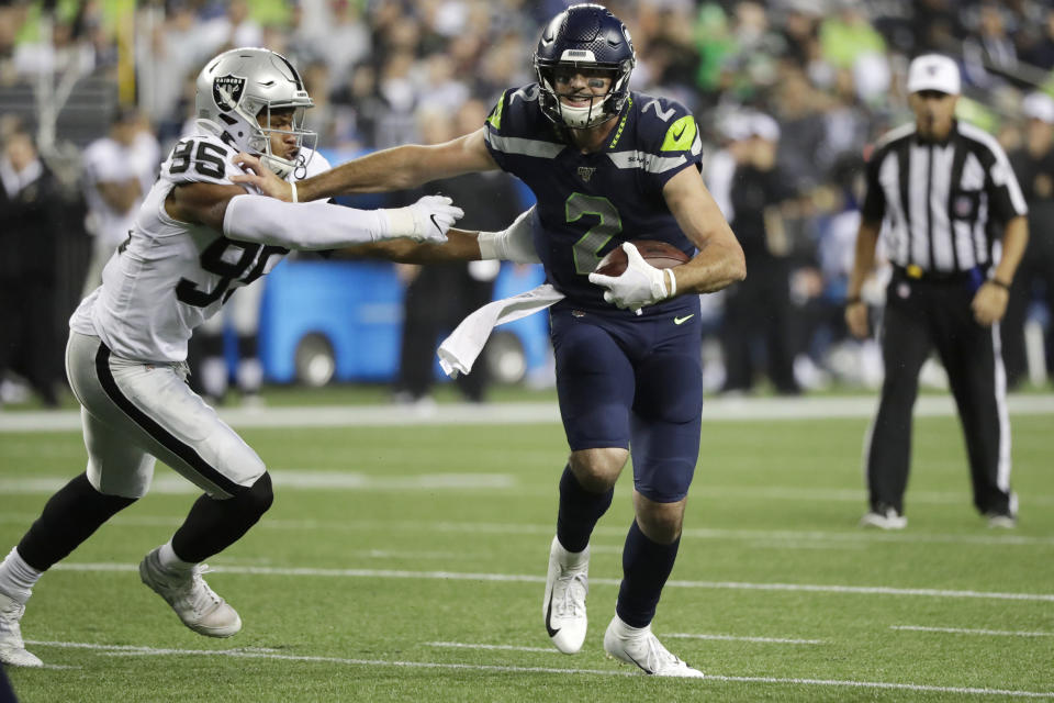 Seattle Seahawks quarterback Paxton Lynch (2) fends off Oakland Raiders defensive end Quinton Bell (95) during the second half of an NFL football preseason game Thursday, Aug. 29, 2019, in Seattle. (AP Photo/Elaine Thompson)