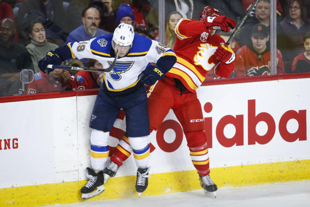 St. Louis Blues' Ivan Barbashev,left, checks Calgary Flames' Michael Stone during the first period of an NHL hockey game in Calgary, Saturday, Nov. 9, 2019. (Jeff McIntosh/The Canadian Press via AP)