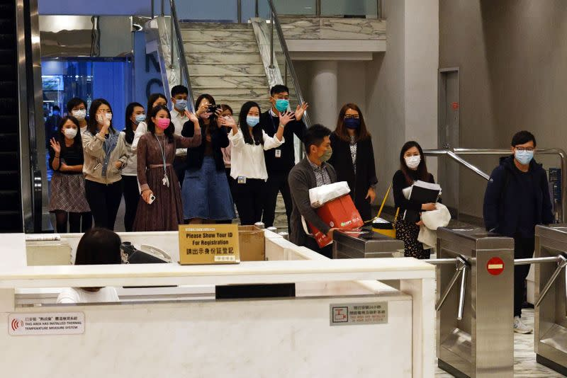 i-Cable TV news journalists leave with their boxes after being laid off in Hong Kong