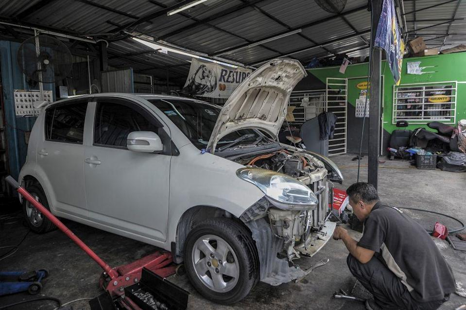 A mechanic repairs a car at his workshop in Kuala Lumpur April 14, 2020. — Picture by Shafwan Zaidon
