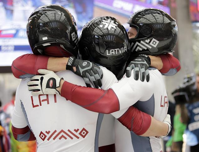 The team from Latvia LAT-1, with Oskars Melbardis, Daumants Dreiskens, Arvis Vilkaste and Janis Strenga, celebrate after they won the silver medal during the men's four-man bobsled competition final at the 2014 Winter Olympics, Sunday, Feb. 23, 2014, in Krasnaya Polyana, Russia. (AP Photo/Jae C. Hong)