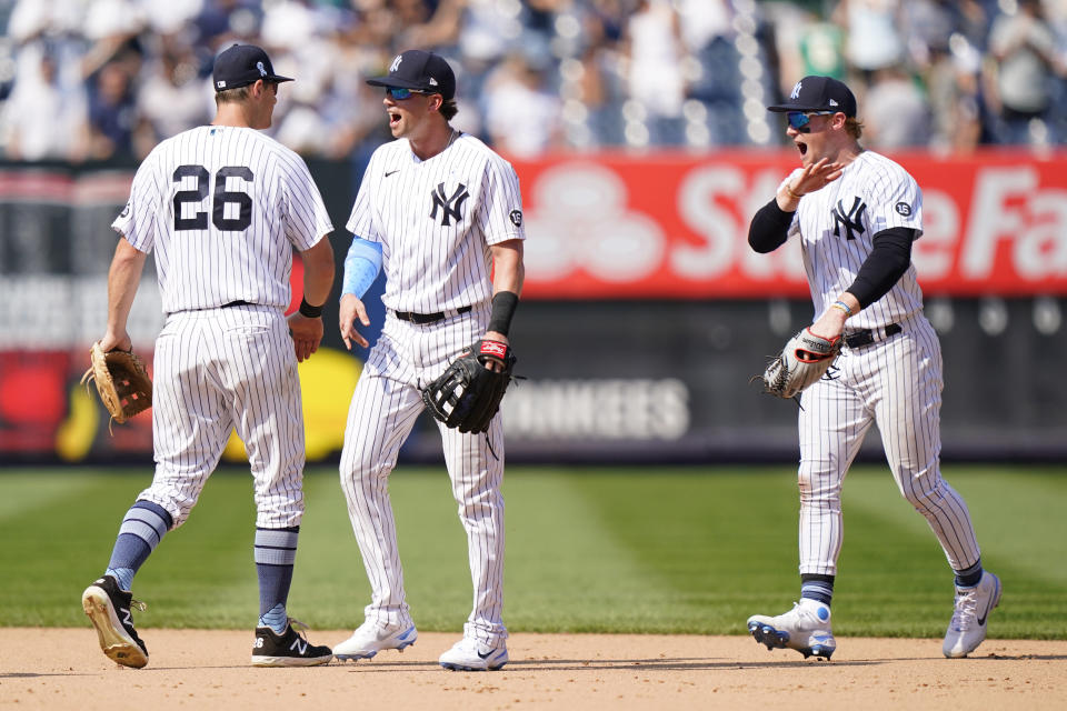 New York Yankees DJ LeMahieu, left, Tyler Wade, center, and Clint Frazier, right, celebrate after the Yankees completed a triple play to defeat the Oakland Athletics in the top of the ninth inning of a baseball game, Sunday, June 20, 2021, at Yankee Stadium in New York. (AP Photo/Kathy Willens)