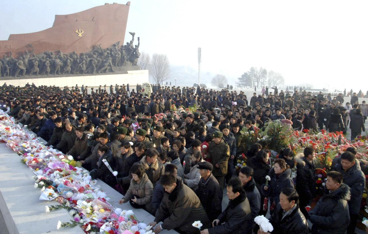 North Koreans offer flowers in front of statues of North Korea's founder Kim Il Sung and former leader Kim Jong Il at Mansudae hill in Pyongyang, on the second anniversary of the death of Kim Jong Il, in this undated photo released by North Korea's Korean Central News Agency (KCNA) in Pyongyang on December 17, 2013. REUTERS/KCNA (NORTH KOREA - Tags: POLITICS ANNIVERSARY) 