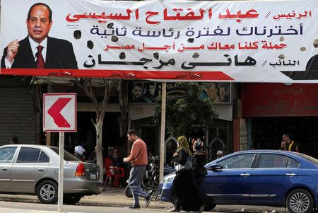 """People walk near a poster depicting Egypt's President Abdel Fattah al-Sisi that reads """"we've chosen you for a second term"""", in Cairo"""